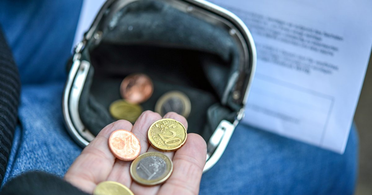 Poor elderly woman is counting some Euro and Cents coins in her hand holding purse and dunning letter - selective focus with little depth of field for adequate copyspace